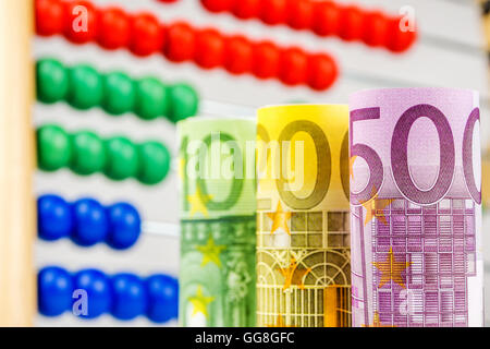 big euro banknotes with big wooden counter in the background as a school equipment and help for children - Stock Photo