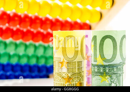 big euro banknotes with big wooden counter in the background as a school equipment and help for children, teaching - Stock Photo