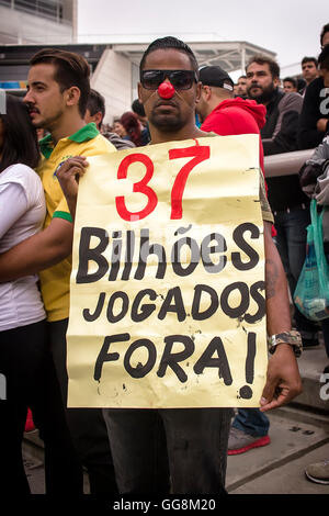 Sao Paulo, Brazil. 3 August 2016. Women's Soccer: Protester holding a sign that says '37 billion thrown away' inside - Stock Photo