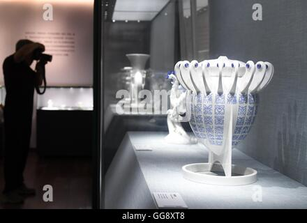 Beijing, China. 10th Aug, 2016. A man takes photos of a porcelain work at the porcelain exhibition of artist Wang - Stock Photo