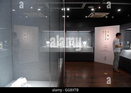 Beijing, China. 10th Aug, 2016. A man views a porcelain work at the porcelain exhibition of artist Wang Xiajun, - Stock Photo