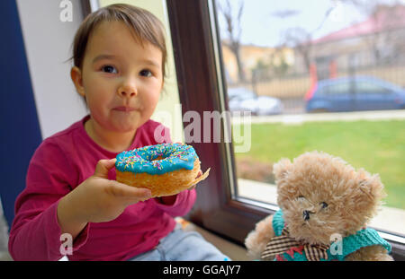little girl eating donuts with her toy friend - Stock Photo