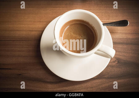 Freshly brewed espresso coffee in white cup on wooden table. Closeup photo with selective focus - Stock Photo