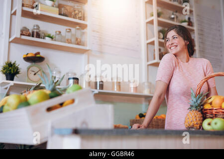 Portrait of beautiful young woman standing behind the counter of her juice bar. Caucasian female working at a juice - Stock Photo