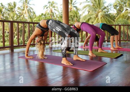 Young women in bridge position at yoga class. Group of young women doing Chakrasana, wheel pose yoga. - Stock Photo