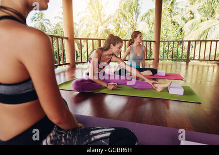 Shot of young women warming up before yoga session. Young people sitting on exercise mat in yoga class. - Stock Photo