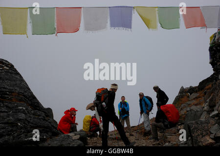 View  of trekkers and Sherpa on route up Zatrwa La Pass in mist at high point with Tibetan prayer flags - Stock Photo