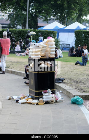 A street side public rubbish bin full to capacity and overflowing with fast food containers - Stock Photo