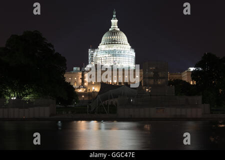 The US Capitol Building under scaffolding as seen across the reflecting pool at night in Washington, DC. - Stock Photo