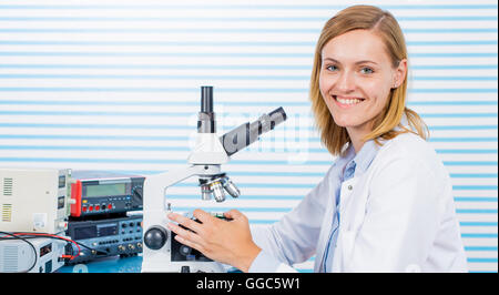 Young woman witch blonde long hair testing blood on RBC, HGB and HCT. laboratory bench which blood sample and microscope - Stock Photo