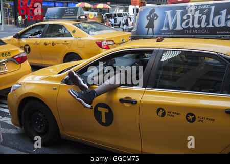 Cab driver rests at a stop light on 7th Avenue in Times Square on a hot summer day. NYC. - Stock Photo