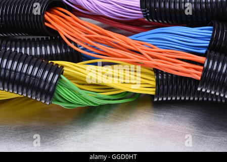 Colorful electric cables and wires in corrugated black plastic pipes used in electrical installation, on metal surface - Stock Photo