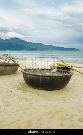Bamboo waterproof round fishing boats on the China Beach in Danang in Vietnam. It is also called Non Nuoc Beach. - Stock Photo