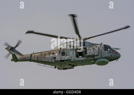 A Royal Navy Agusta Westland Merlin HM.2 helicopter from 814 Naval Air Squadron over Portsmouth Harbour, UK on the - Stock Photo