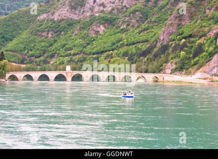 Famous bridge on the Drina in Visegrad, Bosnia and Herzegovina, with large hill - Stock Photo