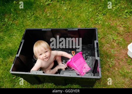 A little girl (2 years old) being bathed in a plastic box while camping - Stock Photo