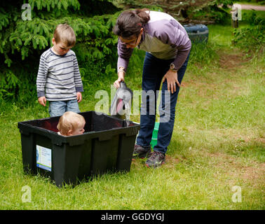 A little girl (2 years old) being bathed in a plastic box while camping Mum adds warm water from a kettle and brother - Stock Photo