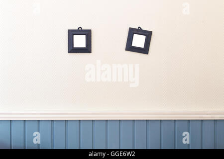 Two small square frames hanging on the white and blue wall. - Stock Photo