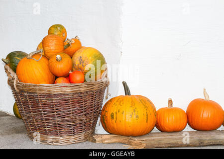 Pumpkins in a wicker basket. Autumn decoration. Outdoors image. - Stock Photo