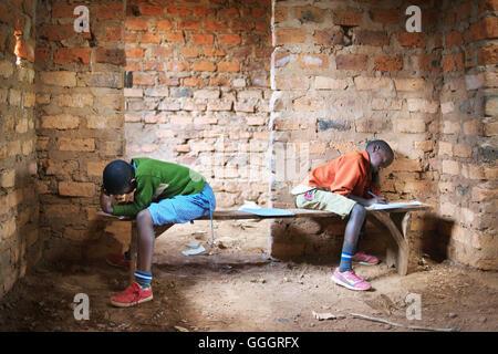 Two african school children in a rural school in Uganda/Rwanda take a school test, sitting opposite each other on - Stock Photo
