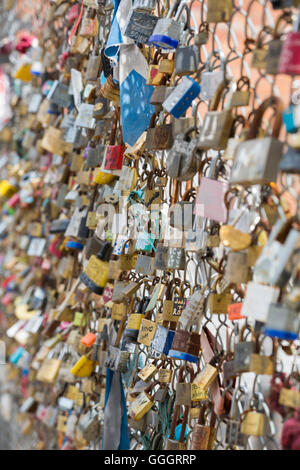 Love padlocks on wire fence at Shoreditch, London in July - Stock Photo