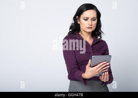 Puzzled woman using a mobile data tablet - Stock Photo