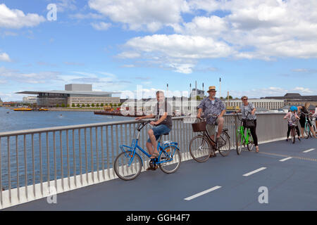 Cycling visitors on the new pedestrian and cyclist bridge, the Inner Harbour Bridge connecting Nyhavn and Christianshavn. - Stock Photo