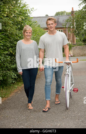 Young couple holding hands walking on a country road - Stock Photo