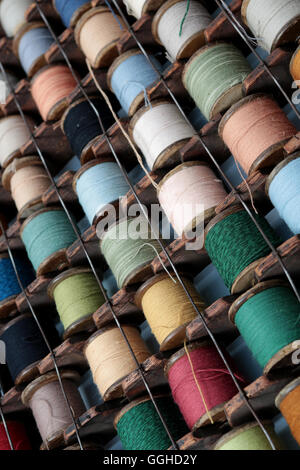 reels of colored cotton stored in European style rack that hangs on the wall - Stock Photo