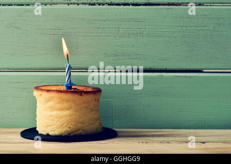 a cheesecake topped with a lit birthday candle, on a rustic wooden surface against a rustic pale green wooden background - Stock Photo