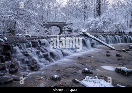 Snow Covered Trees Framing A Stone Bridge And Waterfall During Winter In The Park, Sharon Woods, Southwestern Ohio, - Stock Photo