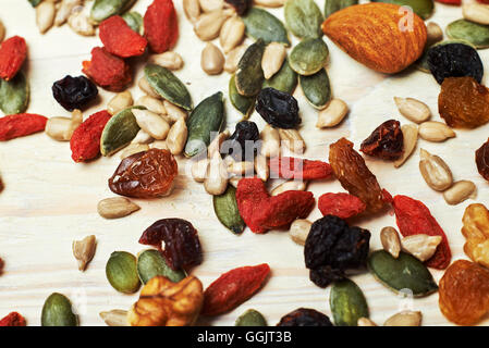 mix nuts seeds and dry fruits, on a wooden table - Stock Photo