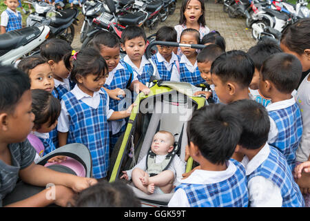 Many Balinese schoolchildren being curious about western baby, girl 5 months old, sitting in a stroller, kids gathering - Stock Photo