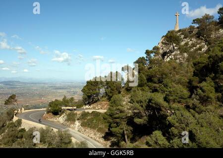 Cyclist on serpentine road with cross of Santuari de Sant Salvador Monastery, near Felanitx, Mallorca, Balearic - Stock Photo