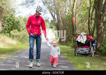 Mother and daughter walking hand in hand, Schorfheide-Chorin Biosphere Reserve, Uckermark, Brandenburg, Germany - Stock Photo