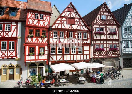 Half-timbered house in the old town with people sitting outside cafes and restaurants, Ochsenfurt, Franconia, Bavaria, - Stock Photo