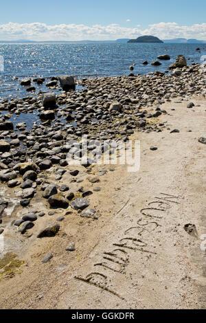 Neuseeland written in the sand on the shore of Lake Taupo at Five Mile Bay, near Waitahanui, Waikato, North Island, - Stock Photo