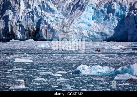 small boat in front of the icefall from the Knud Rasmussen Glacier, East Greenland, Greenland - Stock Photo
