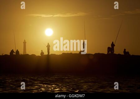 Fishermen on a pier in Rabat at sunset, Morocco - Stock Photo