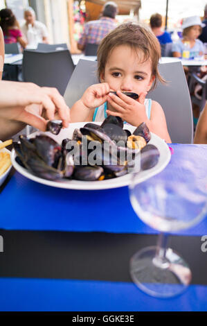 Girl eating mussels, Palavas-les-Flots, Montpellier, Herault, Languedoc-Roussillon, France - Stock Photo