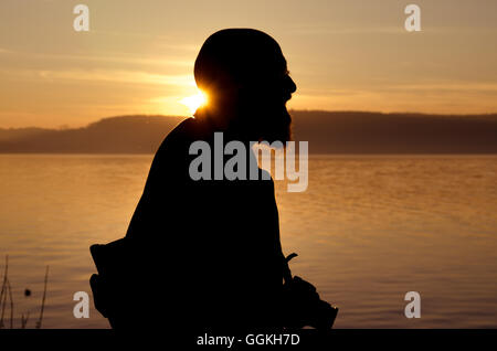 Old man as tourist with camera on Lake Constance at sunset silhouetted - Stock Photo