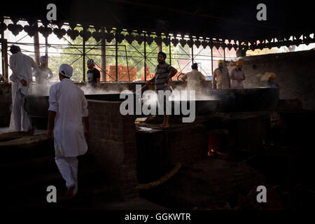 Volunteers prepare food for  worshippers and pilgrims in the kitchen of the Golden Temple complex in Amritsar. © - Stock Photo