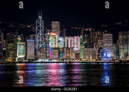 Hong Kong, Hong Kong SAR, China. 25th July, 2016. The lights of the Hong Kong skyline reflects in the water of Victoria - Stock Photo