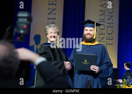Graduation candidate in cap and gown receives diploma at Western Governors University commencement ceremony in Orlando, - Stock Photo