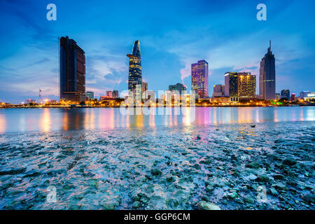 Night view of Business and Administrative Center of Ho Chi Minh city on Saigon riverbank in twilight, Vietnam - Stock Photo