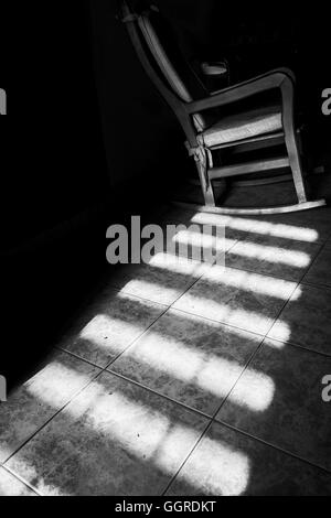 Some light guiding the eyes to an empty chair. - Stock Photo