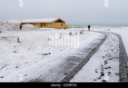 Unrecognized man walking on a snowy road to the yellow winter cottage house in Iceland - Stock Photo