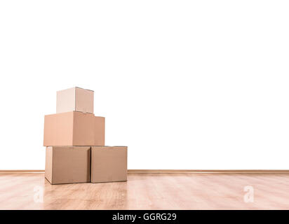 Empty room with a white wall and moving boxes on the floor. - Stock Photo