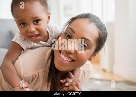 Black mother carrying baby daughter piggyback - Stock Photo