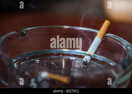 Burning cigarette in an ashtray - Stock Photo